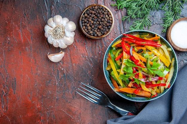 Bovenaanzicht groentesalade in kom ultramarijn blauwe sjaal knoflook zwarte peper vork op donkerrode tafel kopie ruimte
