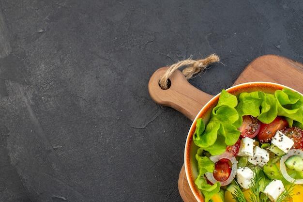 Bovenaanzicht groentesalade met kaas en tomaten op donkere achtergrond