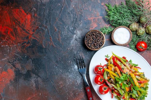 Bovenaanzicht groentesalade op ovale plaat cherry tomaten vork kruiden op donkerrode tafel kopie ruimte