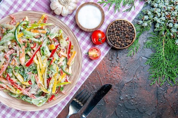 Bovenaanzicht groentesalade op plaat op tafelkleed vork en mes zout en zwarte peper dennen tak op donkerrode tafel