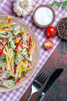 Bovenaanzicht groentesalade op plaat op tafelkleed vork en mes zout en zwarte peper knoflook op donkerrode tafel