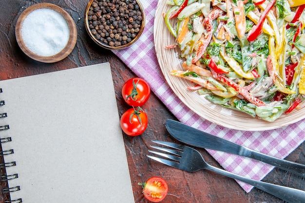 Bovenaanzicht groentesalade op plaat op tafelkleed vork en mes zout en zwarte peper tomaten een notitieboekje op donkerrode tafel