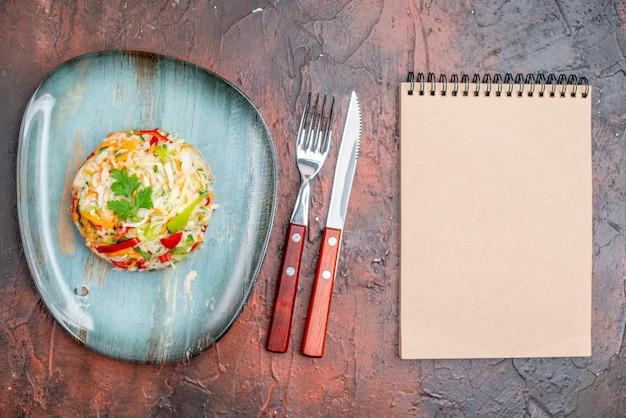 Bovenaanzicht groentesalade rond gevormd binnenbord met bestek op donkere tafel