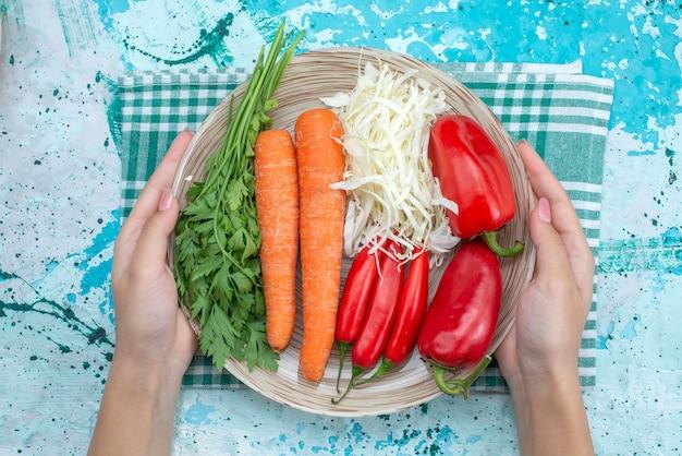 Bovenaanzicht groentesamenstelling kool wortelen greens en rode pittige paprika's op de helderblauwe tafel plantaardig voedsel maaltijd gezonde kleur