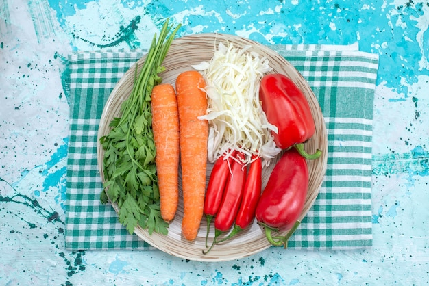 Bovenaanzicht groentesamenstelling kool wortelen greens en rode pittige paprika's op het helderblauwe bureau plantaardig voedsel maaltijd gezonde kleur