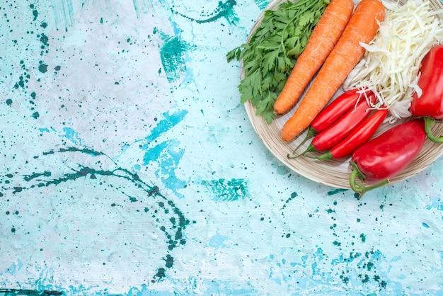 Bovenaanzicht groentesamenstelling kool wortelen greens en rode pittige paprika's op het heldere bureau plantaardige voedsel maaltijd gezonde kleur