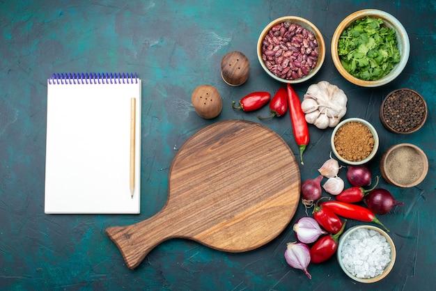 Bovenaanzicht groentesamenstelling met greens en kruiderijen blocnote op de donkerblauwe kleur van de maaltijd op het bureau