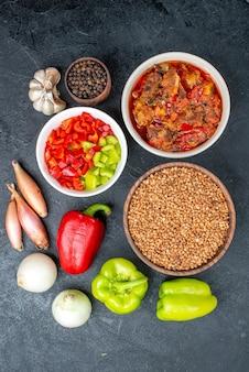 Bovenaanzicht groentesoep met boekweit en verse groenten op grijs