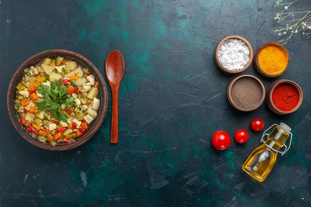 Bovenaanzicht groentesoep met greens samen met kruiden en olijfolie op donkere achtergrond
