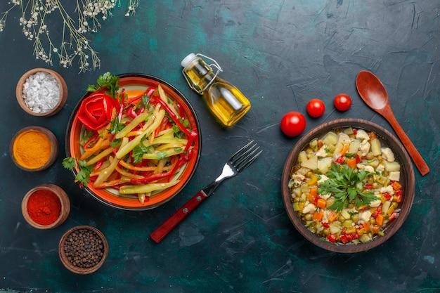 Bovenaanzicht groentesoep met verschillende kruiden en pittige salade op donkerblauwe achtergrond