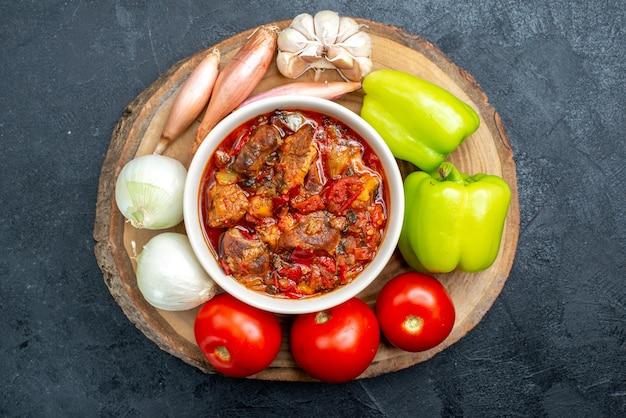 Bovenaanzicht groentesoep met verse groenten op de grijze