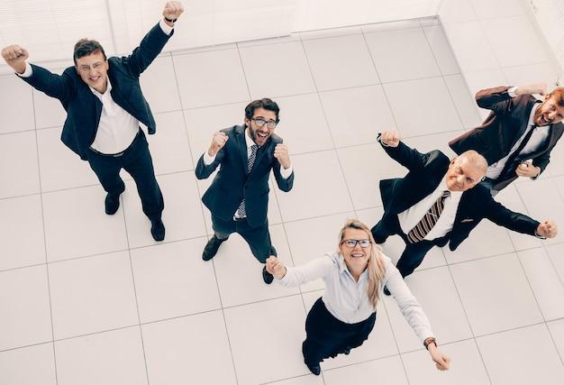 Bovenaanzicht groep gelukkige mensen die hun succes laten zien