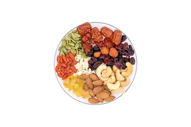 Bovenaanzicht groep van volle granen en gedroogd fruit in een glasplaat geïsoleerd op een witte achtergrond.