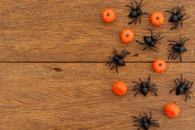Bovenaanzicht groep zwarte jachtspinnen en pompoenen lag op een bruine retro houten tafelbladachtergrond