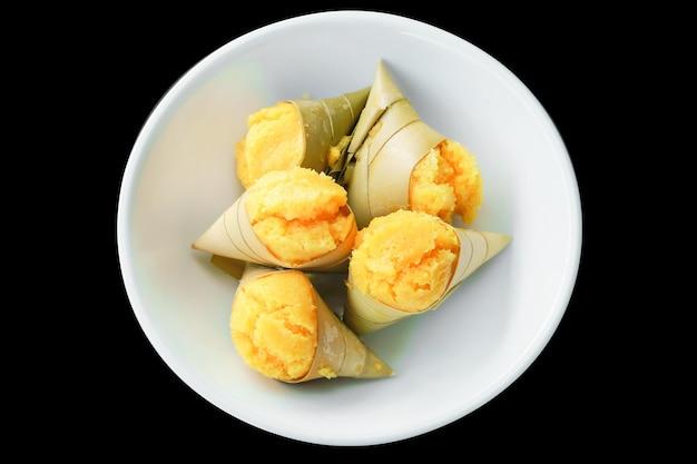 Bovenaanzicht grog palmcake omwikkeld met bananenblad in witte ronde kom.