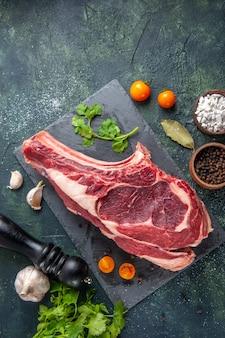Bovenaanzicht groot vleesplak rauw vlees met peper en groen op donkere ondergrond