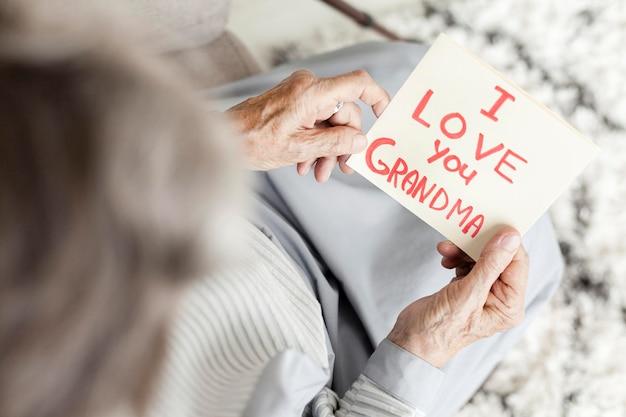 Bovenaanzicht grootmoeder kijken naar verjaardagsgroet