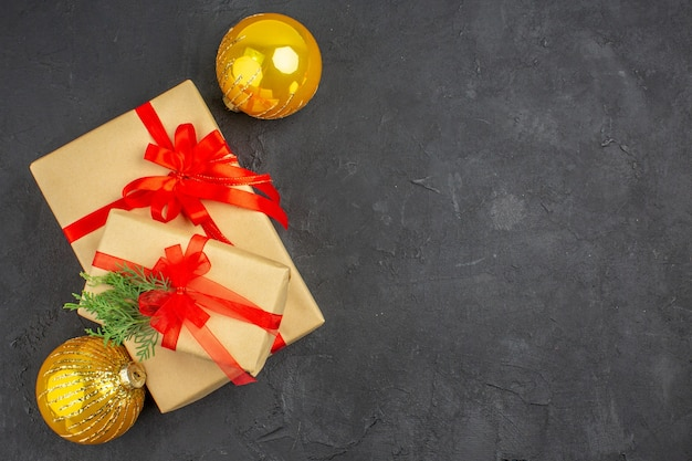 Bovenaanzicht grote en kleine kerstcadeaus in bruin papier gebonden met rode lintballen op een donkere ondergrond