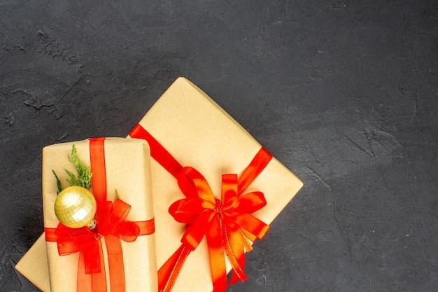 Bovenaanzicht grote en kleine kerstcadeaus in bruin papier gebonden met rood lint bal op donkere ondergrond