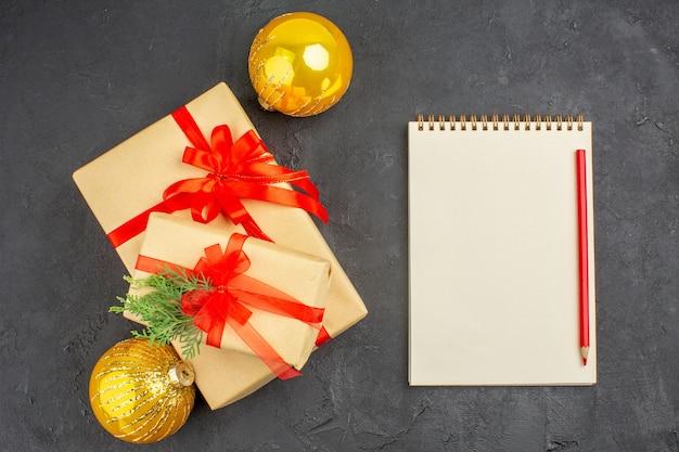 Bovenaanzicht grote en kleine kerstcadeaus in bruin papier gebonden met rood lint ballen notebook potlood op donkere ondergrond
