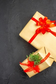 Bovenaanzicht grote en kleine kerstcadeaus in bruin papier gebonden met rood linttakspar op donkere ondergrond
