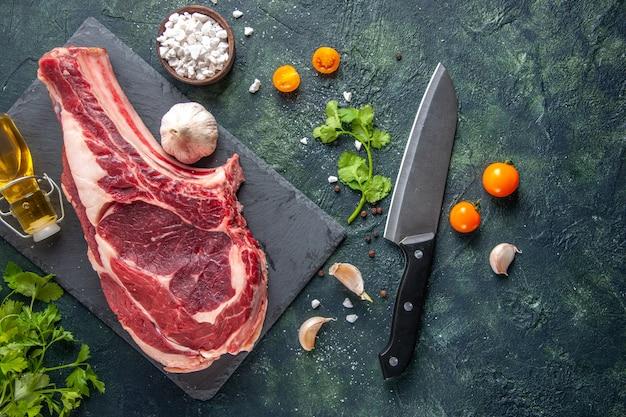 Bovenaanzicht grote vleesplak rauw vlees met greens op donkere ondergrond