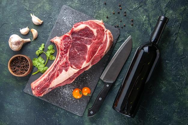 Bovenaanzicht grote vleesplak rauw vlees met peper op donkere ondergrond