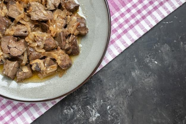 Bovenaanzicht half gebakken lever en ui op ovale plaat op tafelkleed