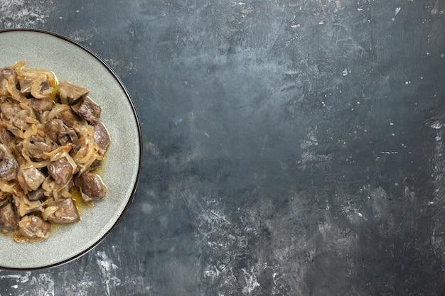 Bovenaanzicht half gebakken lever en ui op ovale plaat