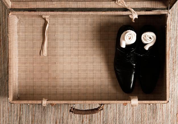 Bovenaanzicht half lege vintage koffer met casual kleding