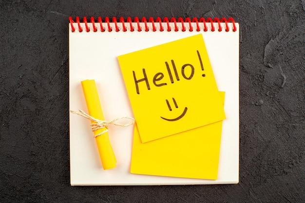 Bovenaanzicht hallo geschreven op notitie op notitieblok opgerolde notitie vastgebonden met touw op zwarte tafel