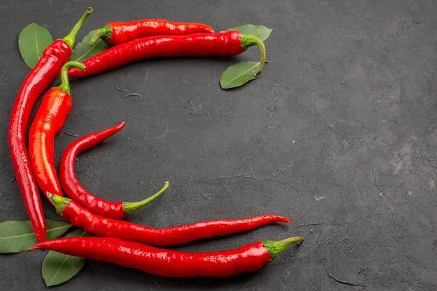 Bovenaanzicht halve cirkel van rode hete pepers en laurierblaadjes aan de rechterkant van de zwarte tafel