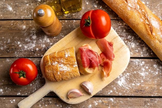 Bovenaanzicht ham, brood en tomaten op een houten bord