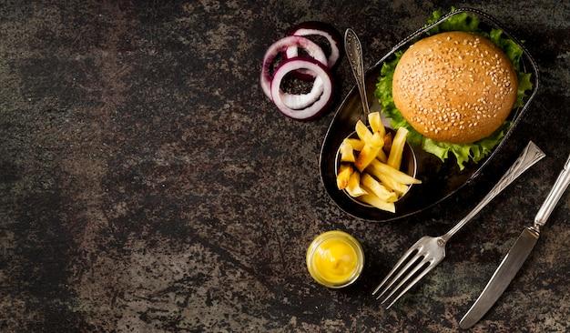 Bovenaanzicht hamburger en frietjes met bestek en kopie-ruimte