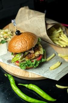 Bovenaanzicht hamburger met frietjes en groene paprika op blackboard