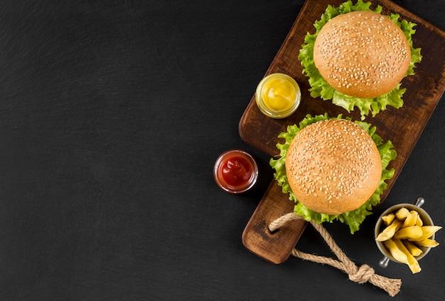 Bovenaanzicht hamburgers en frietjes op snijplank met kopie-ruimte