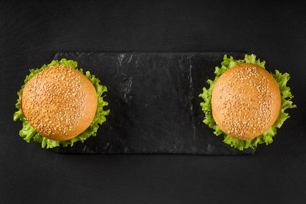 Bovenaanzicht hamburgers op leisteen bord