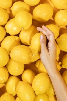 Bovenaanzicht hand bovenop citroenen