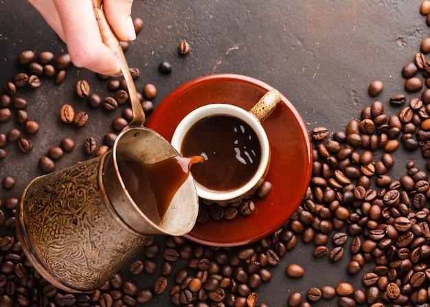 Bovenaanzicht hand gieten koffie in cup