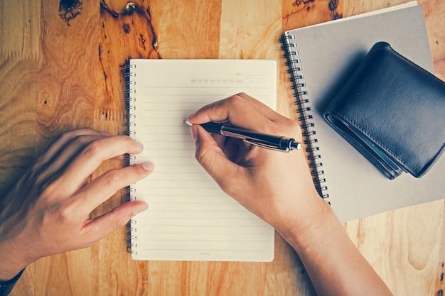 Bovenaanzicht. hand het schrijven van boeken portemonnee en laptop geplaatst op een houten tafel.