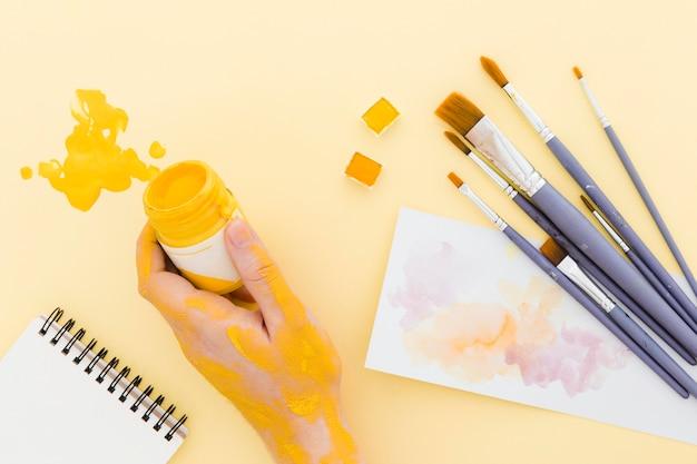 Bovenaanzicht hand met aquarel verf