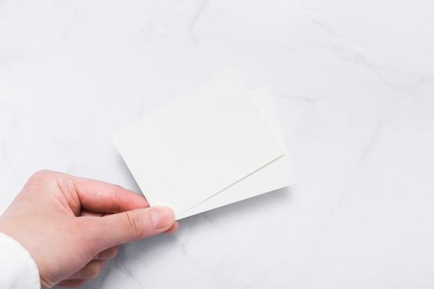 Bovenaanzicht hand met blanco visitekaartje
