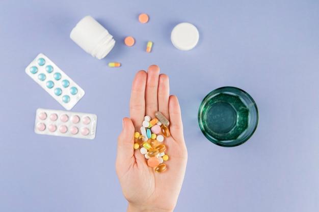 Bovenaanzicht hand met collectie van medicijnen