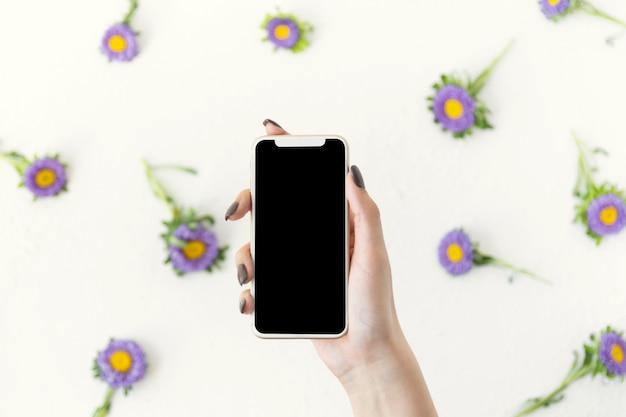 Bovenaanzicht hand met een telefoon omringd door bloemen