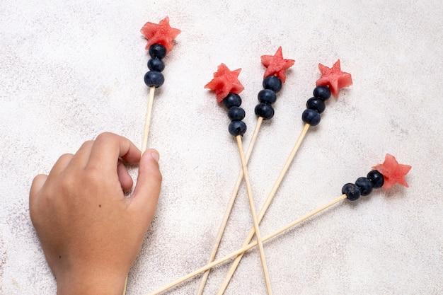 Bovenaanzicht hand met fruitspiesjes