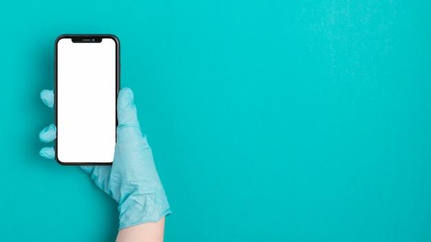 Bovenaanzicht hand met mobiele telefoon met kopie ruimte