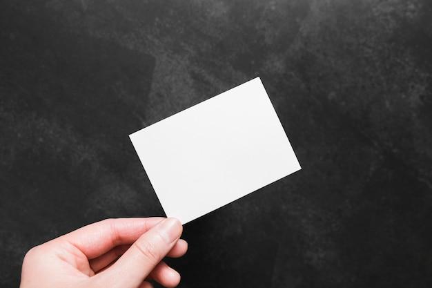 Bovenaanzicht hand met papieren visitekaartje