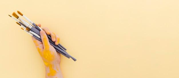 Bovenaanzicht hand met penselen met kopie ruimte