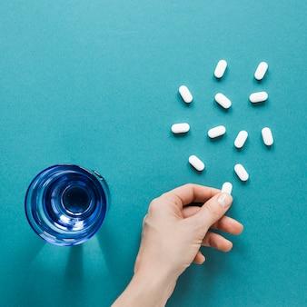 Bovenaanzicht hand met pijnstillers op de tafel