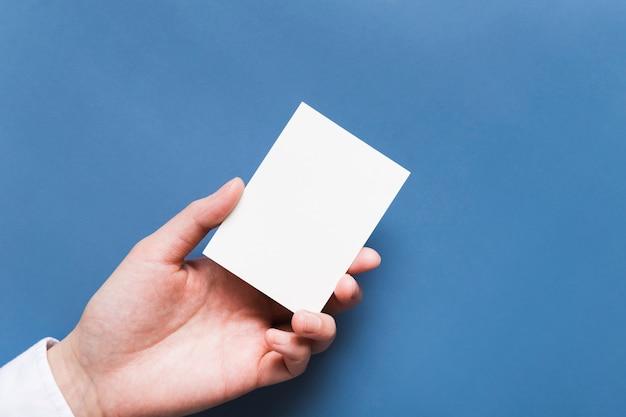 Bovenaanzicht hand met visitekaartje